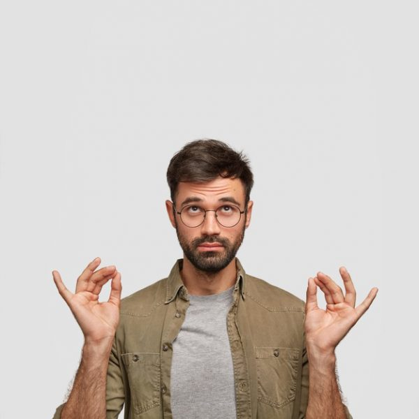 concentrated-unshaven-guy-believes-good-fortune-makes-mudra-sign-with-both-hands-meditates-after-work_273609-15403